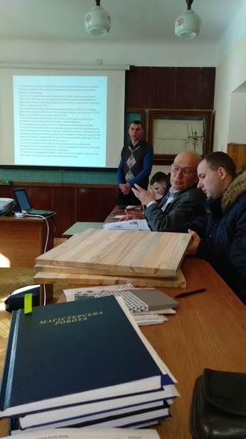 Присутні на захисті обговорюють конструкцію меблевих щитів виготовлених із вживаної деревини